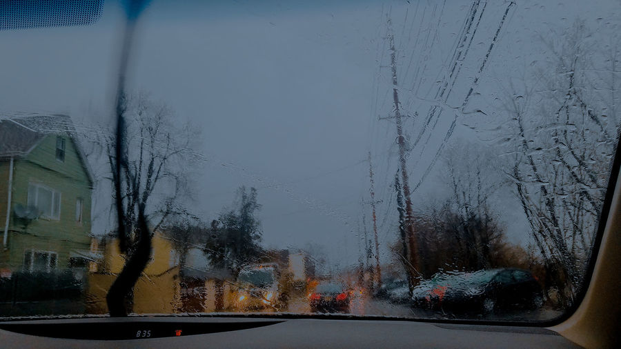 Road seen through car windshield during rainy season