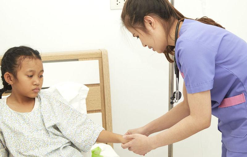 Nurse examining patient at home
