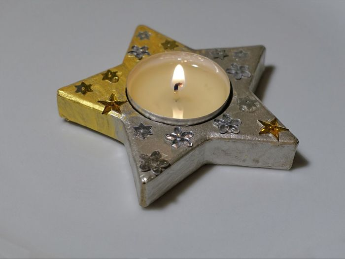 Close-Up Of Star Shape Tea Light Candle On Gray Background
