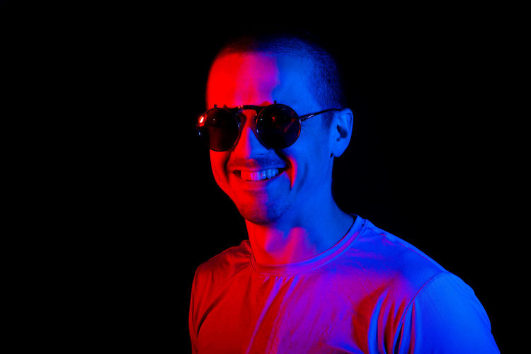 Portrait of man wearing sunglasses against black background