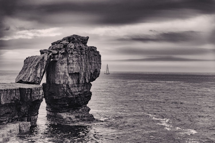 Rock And Boat Seascape Seaside No People Nature Outdoors Dramatic Sky Cloud - Sky Rock - Object Sailing Boat Rock In The Sea Rock Yacht Quarrying Relic The Great Outdoors - 2017 EyeEm Awards