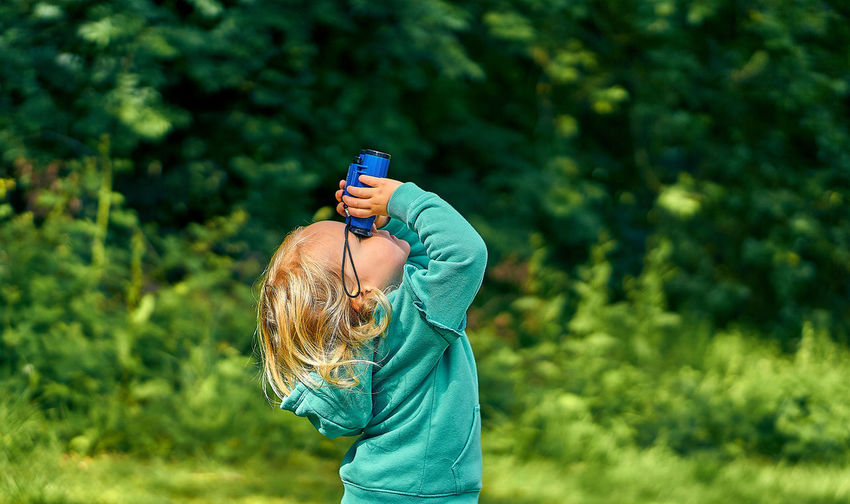 Side view of girl looking through binoculars while standing on land