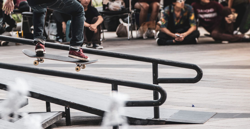 Low Section Of Man Skateboarding On Railing