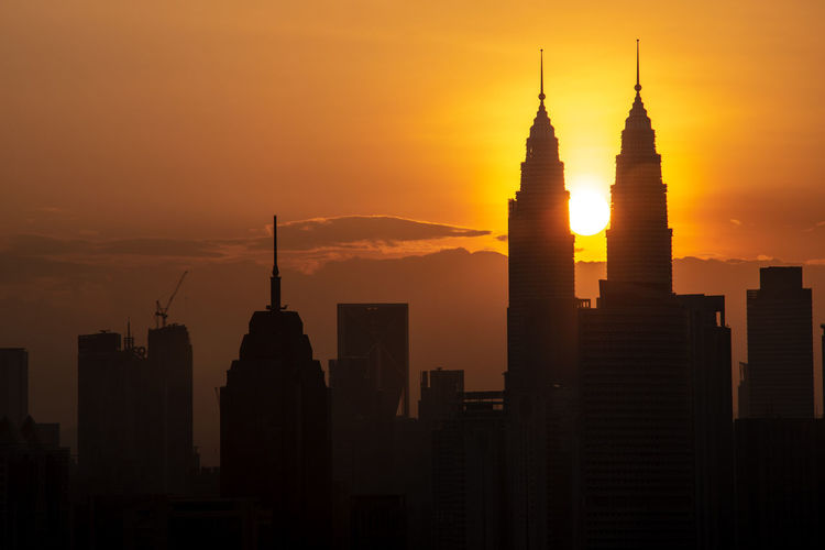 Silhouette of buildings in city during sunset