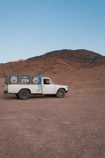 Vintage car on desert against clear blue sky