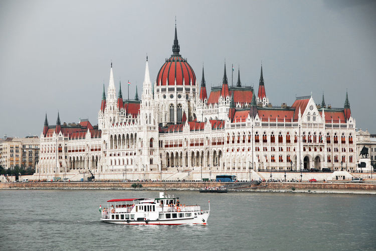 Boat in river by hungarian parliament building in city