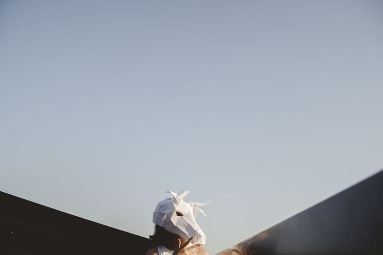 Low angle view of a girl wearing a animal mask against the sky
