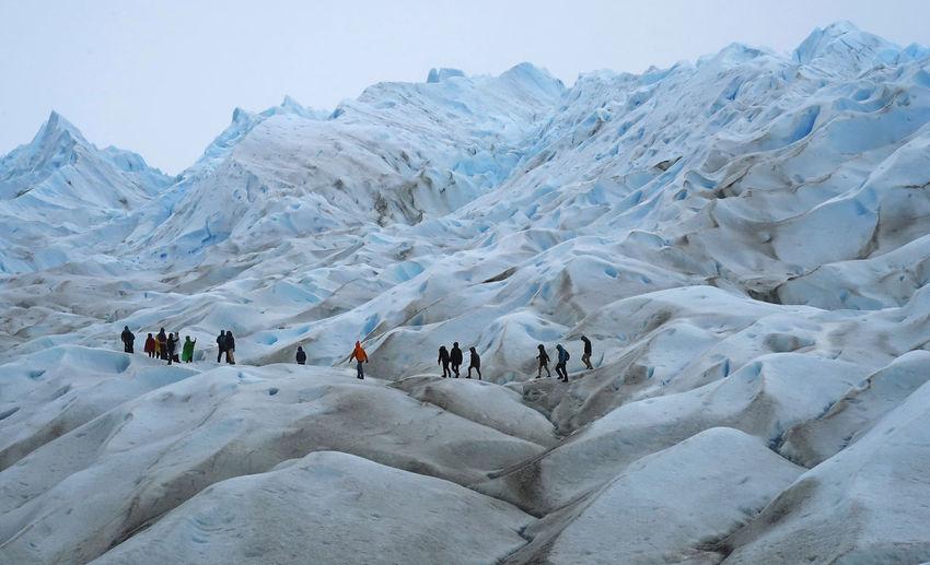 People walking on glacier during winter