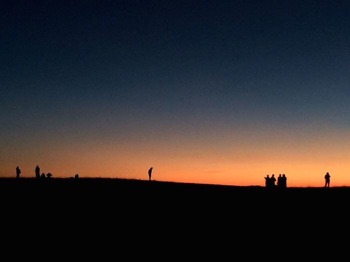 Silhouette people on mountain against clear sky at dusk