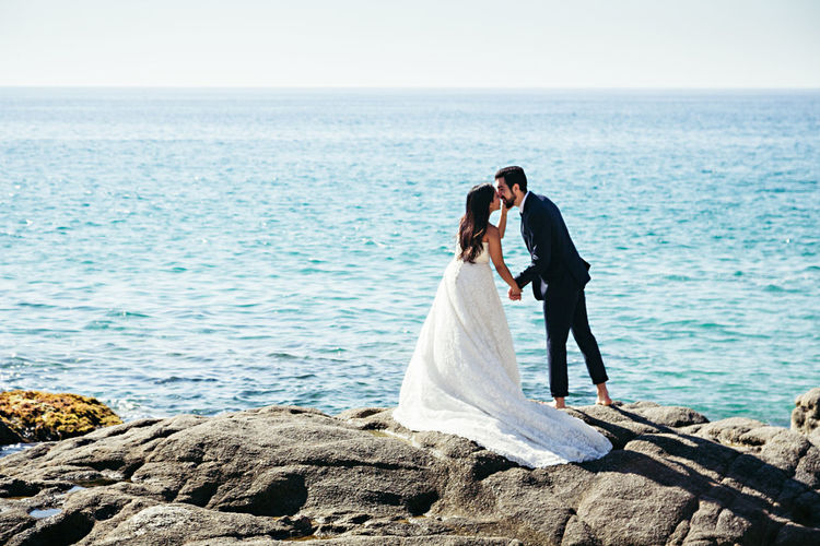 Newlywed Couple Kissing While Standing At Rocky Beach Against Clear Sky