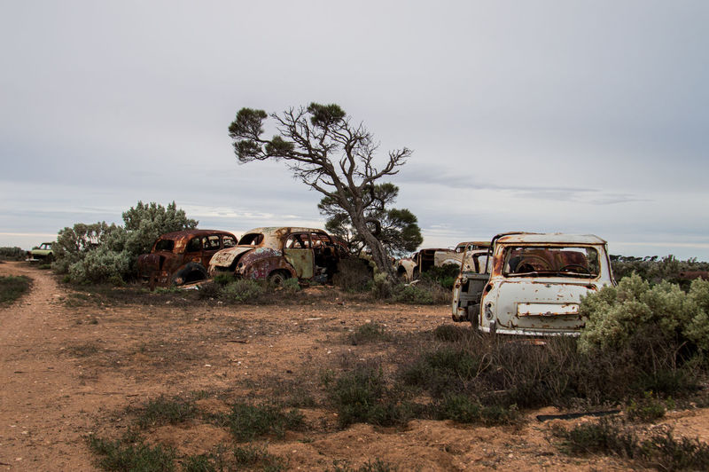 Abandoned vehicles on field against sky outback australia