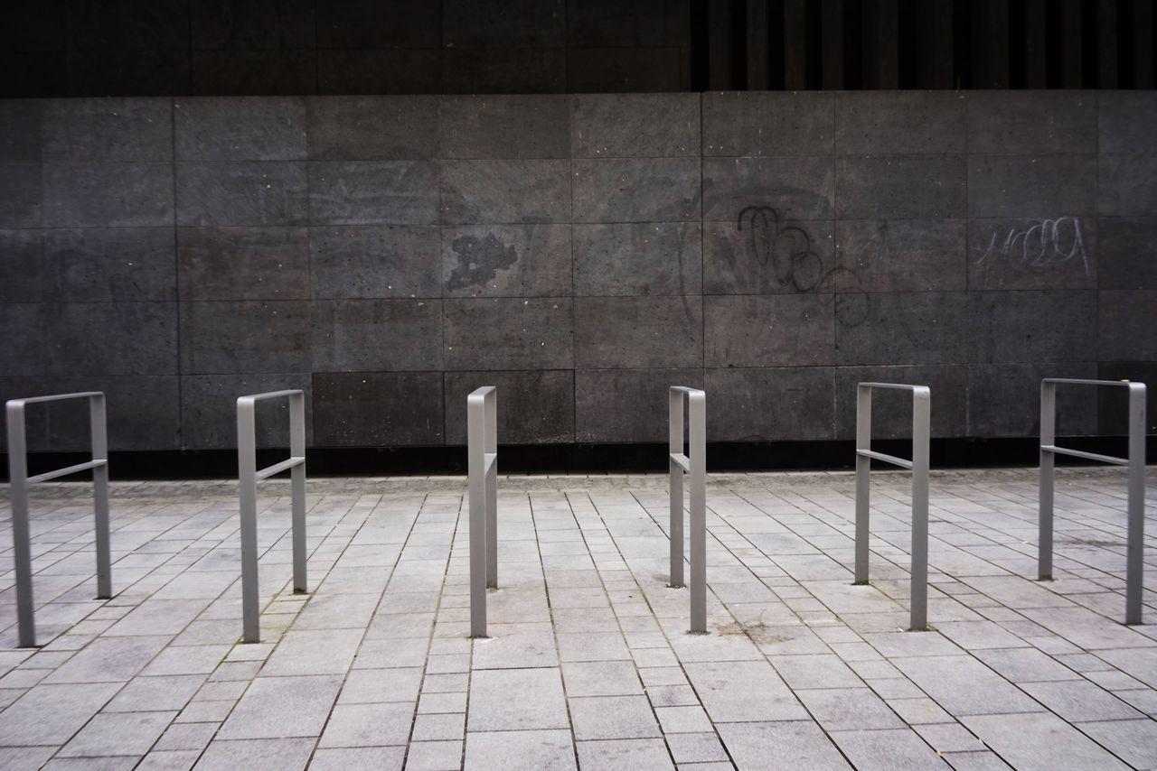 Metallic Railings On Footpath Against Wall