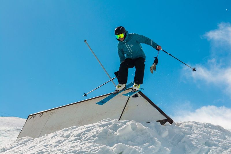 Low angle view of man skiing on snowcapped mountain against sky