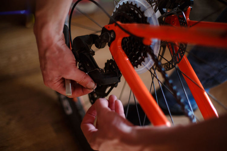 Hand of a man with a multitool near the wheel and brakes of the bike. bike repair, setting up disc