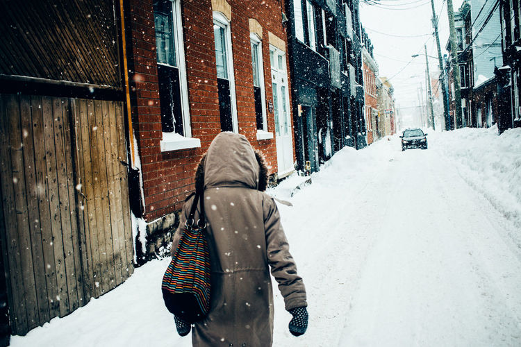 Rear view of woman walking in snow