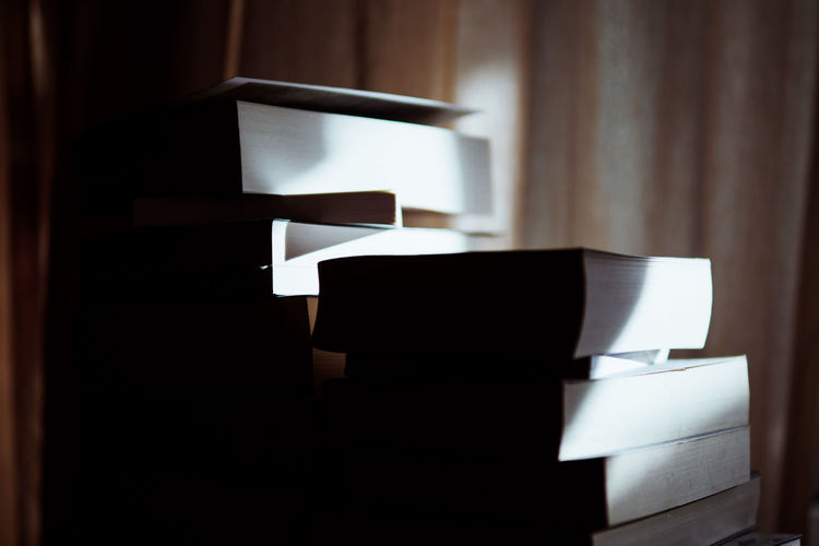 Close-Up Of Sunlight Falling On Stacked Books At Library