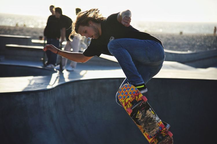 Full length of young man skateboarding at park against sky