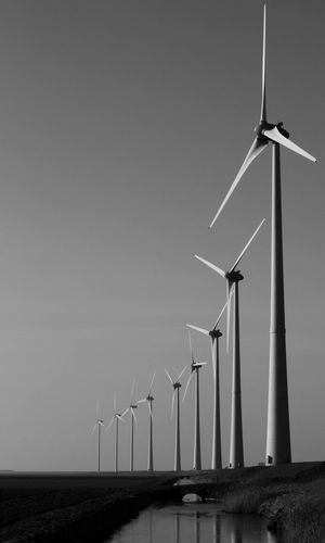 Windmills in row on field against sky