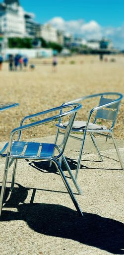 who's in the hot seat? Eastbourne United Kingdom East Sussex Beach Walk & Then Rest. Seafront View Ice Cream Beach Shop Metal Chairs Chairs In The Sun Got Too Hot To Sit On Beach Sunlight Shadow Water Close-up Sky