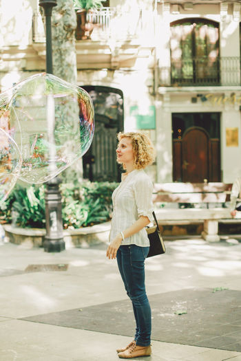 Woman standing by huge bubbles on footpath in city