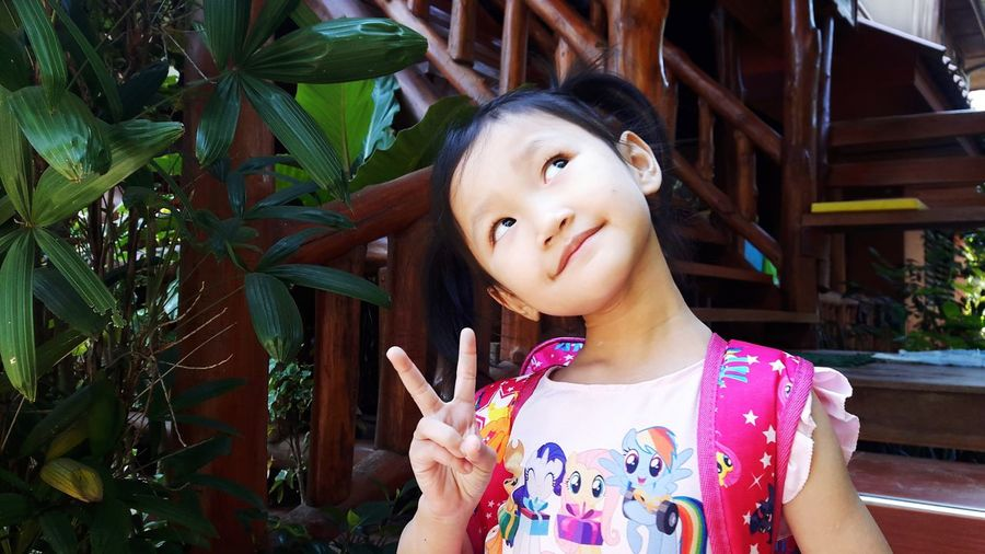 A four-year-old asian girl is posing with a two-inch eye on her.