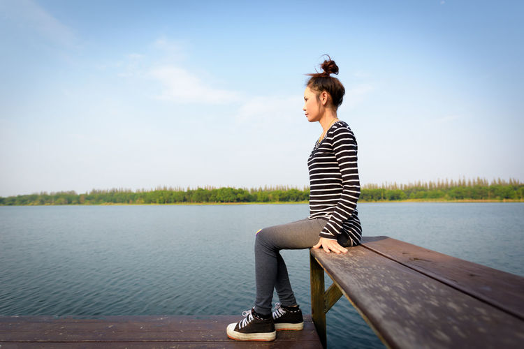 Side view of woman sitting on pier over lake against sky
