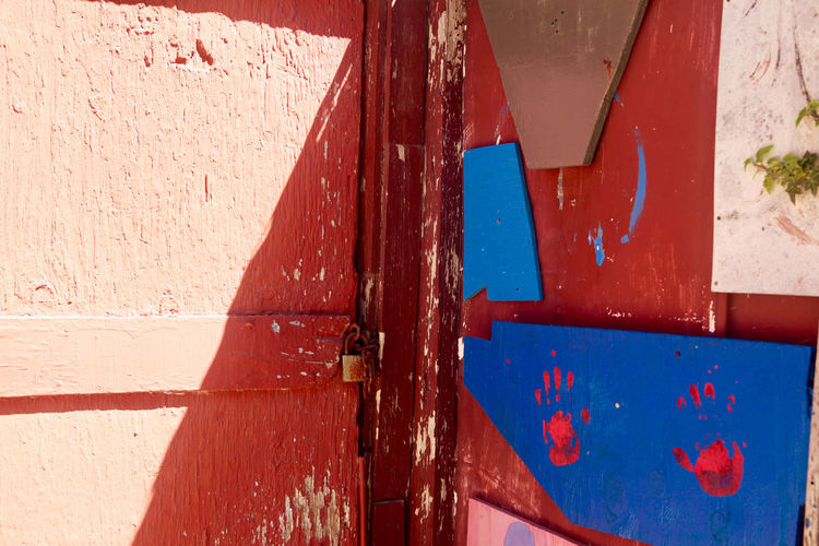 Architecture Blue Building Exterior Built Structure Close-up Day Door Entrance Handprints On Wall Metal Nature No People Old Outdoors Painted Hands Red Shadow Sunlight Wall Wall - Building Feature Weathered Wood - Material