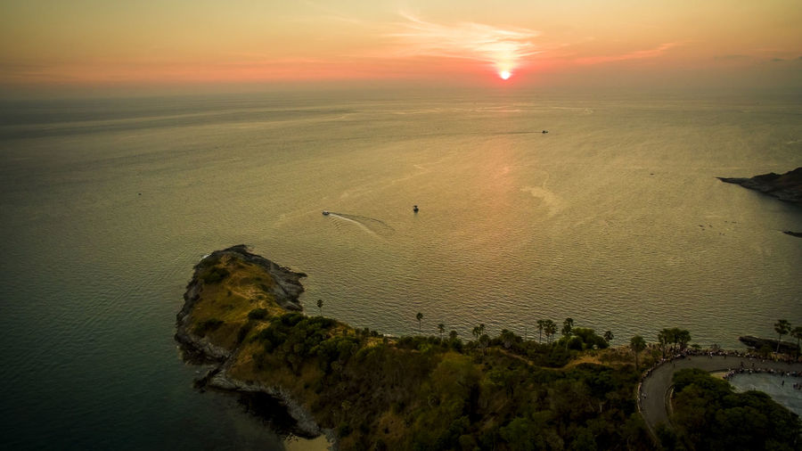 high angle view of beautiful sunset at laem phomthep phuket southern of thailand Phuket Thailand Sunset Sun Sun Set Sundown Evening Awesome Dramatic Sea Ocean Marine Andaman Sky Skies Sailing Ship Yacht Yachting Beautiful Nature Natural Horizon Horizontal Drone  Droneshot Aerial Above Top Top View Light Silhouette Water Vessel Nautical Cape  Laem Phomthep Scene Scenic Scenery Travel Traveling Destination