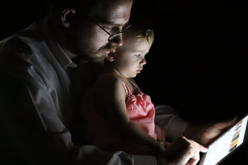 Father With Baby Girl Using Digital Tablet In Darkroom