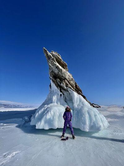 Girl standing in snow against blue sky