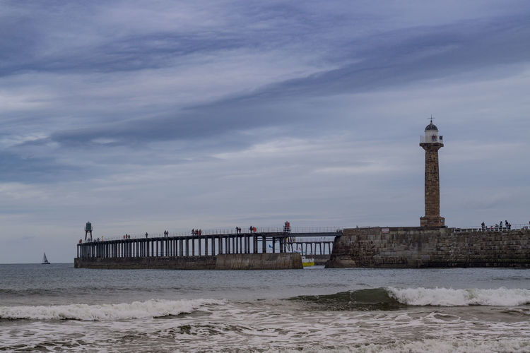 Whitby Whitby Harbour Yorkshire North Yorkshire Yorkshire Coast Uk England Europe Tower Lighthouse Guidance Motion Beach Travel Destinations Pier Wave Travel Cloud - Sky Sea Sky Building Exterior Built Structure Water Building Nature