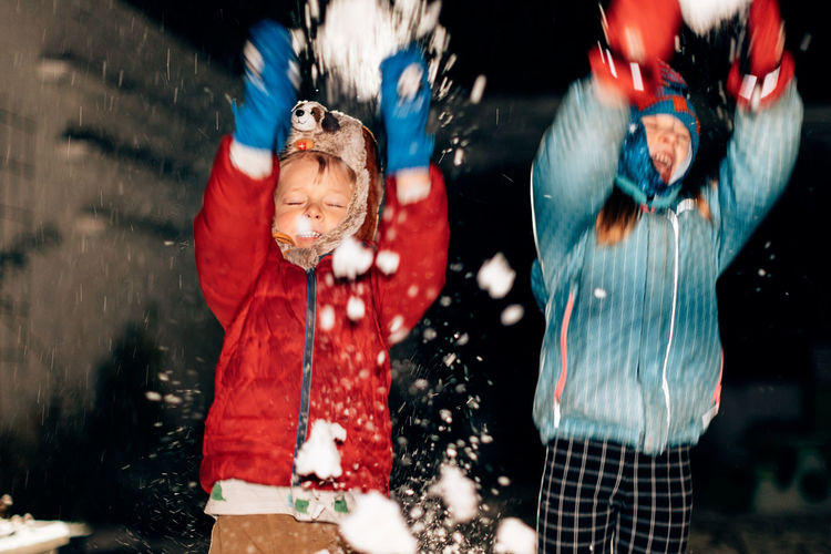 Kids playing with the snow outdoor in the backyard on a cold night