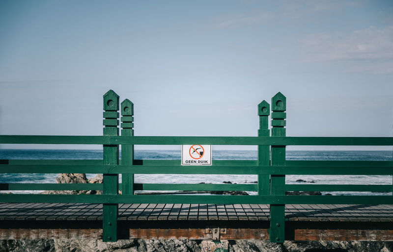 Geen Duik (no diving) Beach Blue Day Engineering Green Nature No People Outdoors Sky Tranquility Walkway Wood Wooden Post