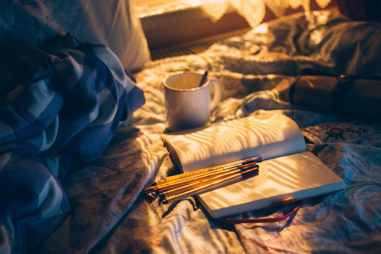 Coffee cup by book and pencils on bed at home
