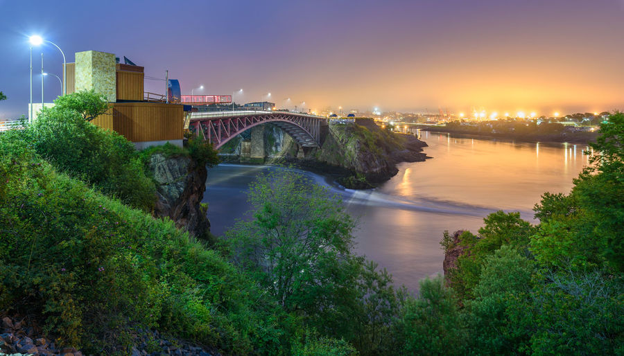 Reversing Falls, New Brunswick New Brunswick, Canada New Brunswick Night Photography Reversing Falls Water Reflections Architecture Beauty In Nature Bridge Bridge - Man Made Structure Building Exterior Built Structure Canada City Connection Illuminated Long Exposure Nature Night No People Outdoors River Sky Sunset Tree Water
