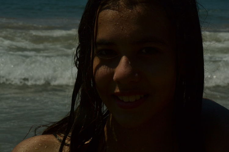 Portrait of smiling teenage girl at beach