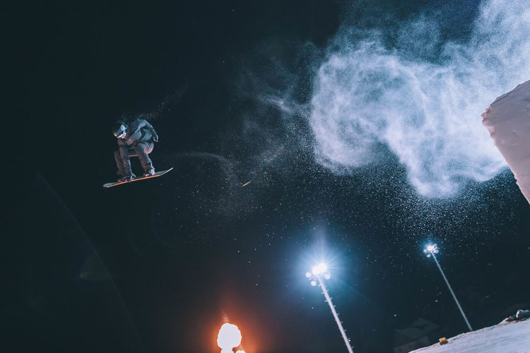 Low Angle View Of Man Snowboarding Against Sky At Night