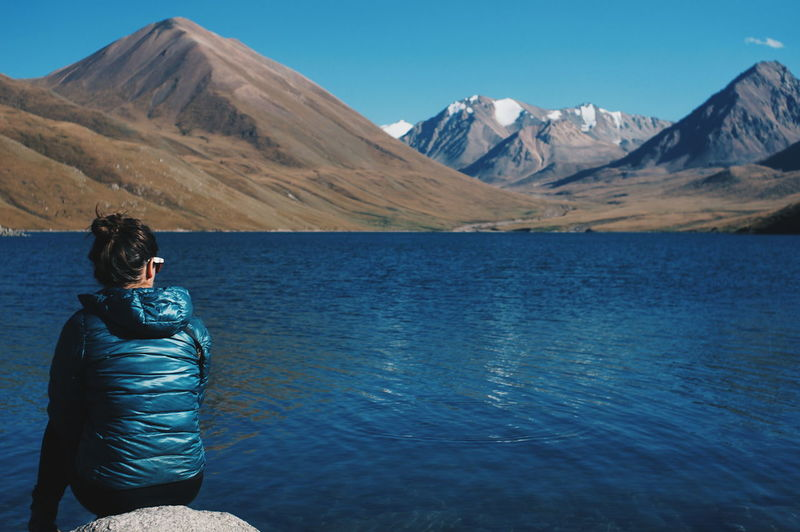 Rear view of woman relaxing on kol ukok lakeshore against mountains