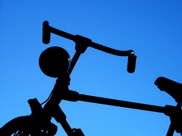 Low angle view of silhouette cross against clear blue sky