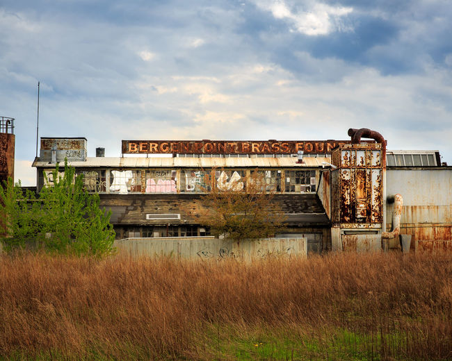 Abandoned Bergen Point Brass Foundry On Field Against Sky