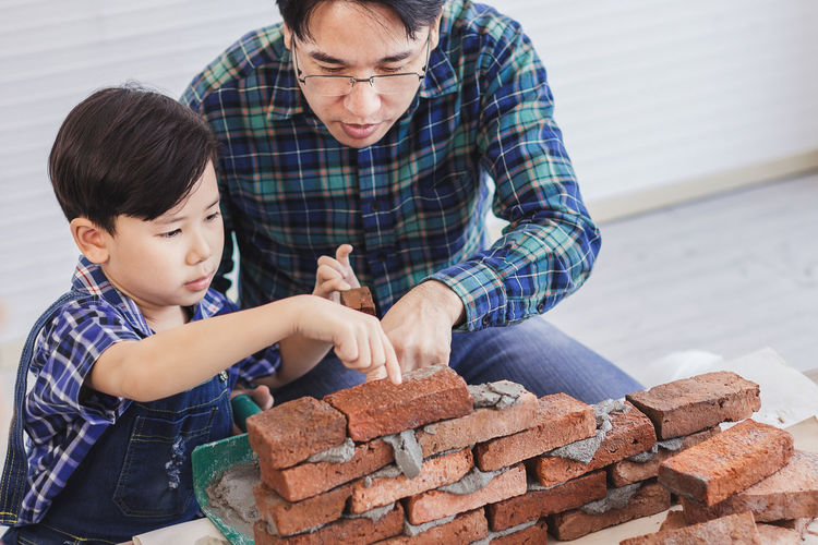 Father teaching son to make brick wall at workshop