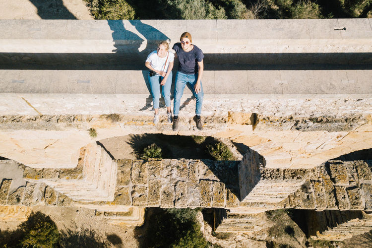 High Angle View Of Friends Sitting On Retaining Wall