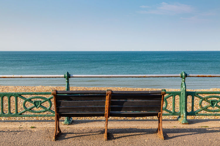Empty Bench Against Sea At Beach