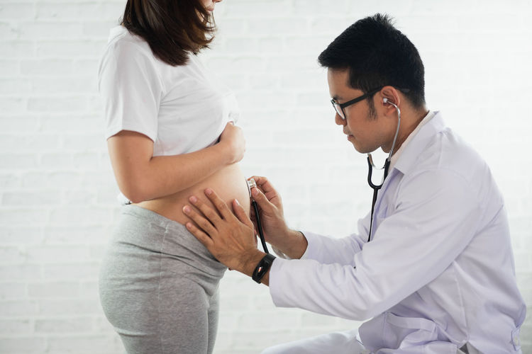 Doctor examining pregnant woman in hospital