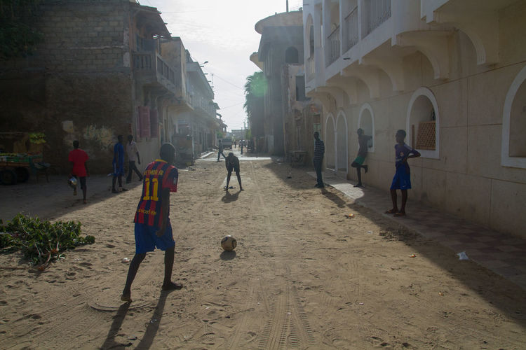 Adult Architectural Column Architecture Building Building Exterior Built Structure City Crowd Day Group Of People Leisure Activity Lifestyles Men Nature Outdoors People Real People Saint Louis Saint Louis Sénégal Senegal Street Street Football Walking Women