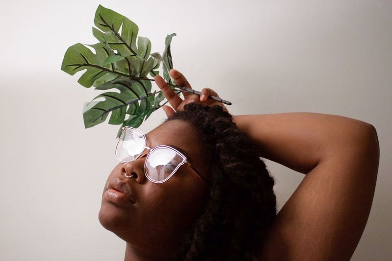Young Women Holding Artificial Leaf While Looking Away Against Wall