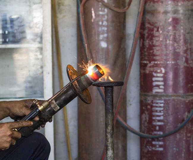 Cropped hands of welder welding in factory