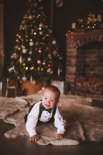 Cute baby boy crawling on floor against christmas tree at home