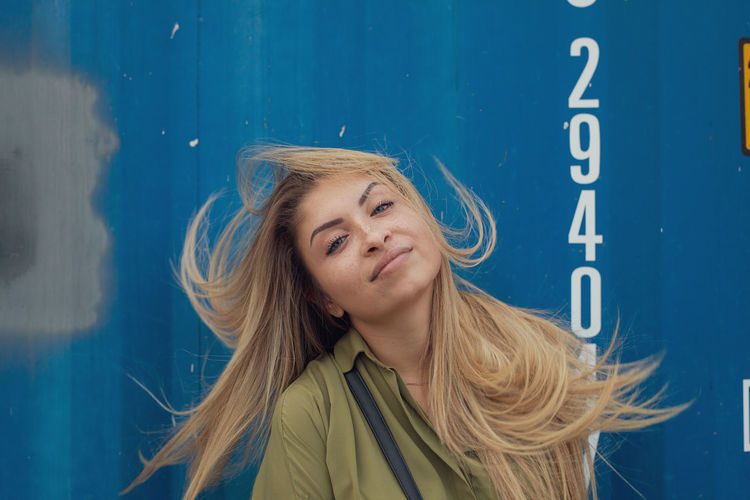 Portrait of young woman tossing hair against blue wall
