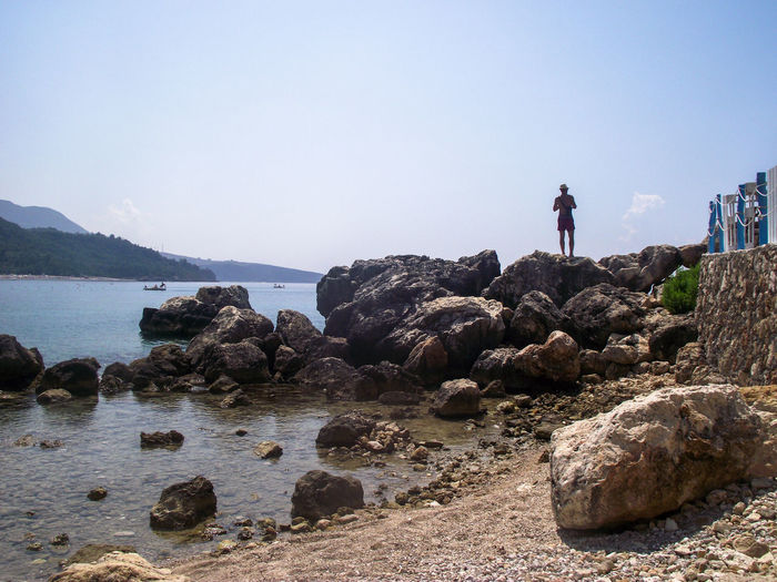 Man standing on rocks by sea against clear sky